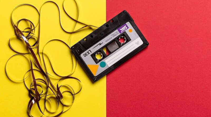 black-cassette-tape-on-top-of-red-and-yellow-surface-1626481